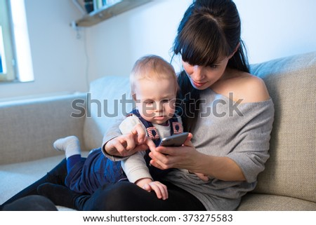 Mother is showing to her curious baby boy cell phone on the couch in the living room. Interaction between baby and woman. Blue cold light from window. Color toned image. First touch with technology. - stock photo