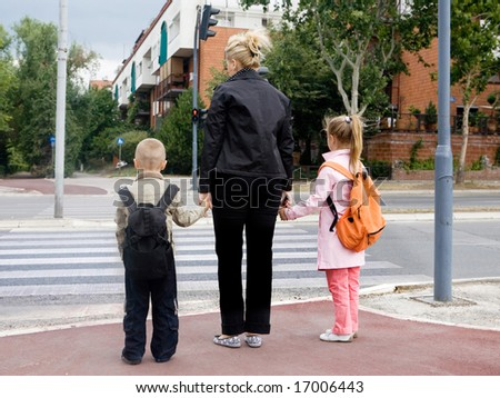 mother is taking children across the street - stock photo
