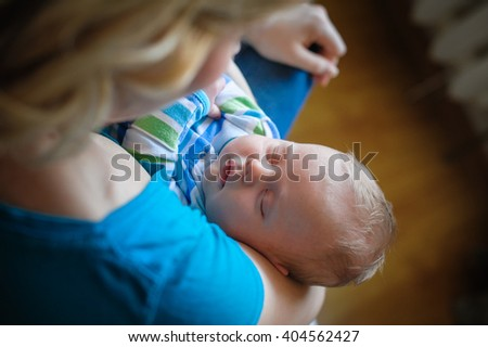 Mother keeps a sleep little baby boy in her arms - stock photo