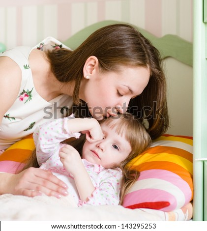 mother kissing a sick child - stock photo