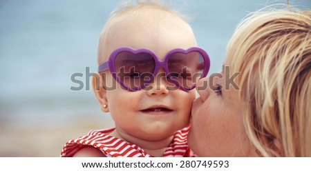 Mother kissing baby on beach - stock photo