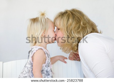 Mother Kissing Daughter - stock photo