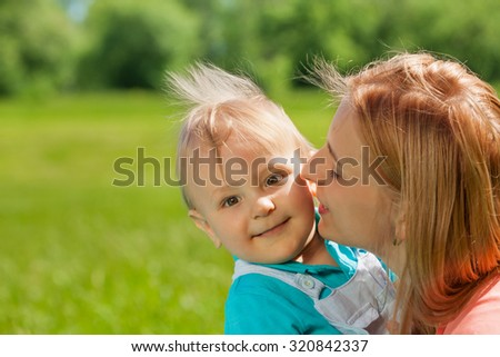 Mother kissing her child in cheek during summer - stock photo