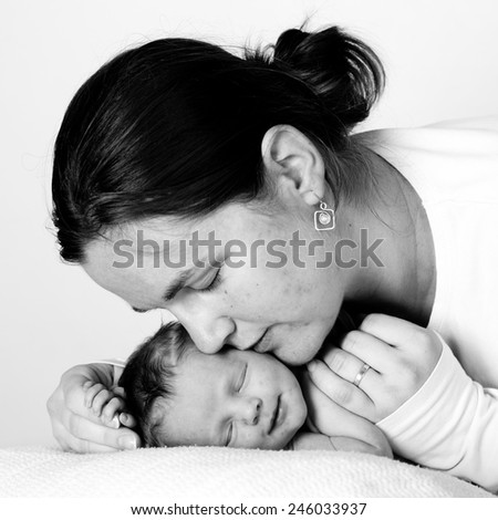 Mother kissing her child studio shot  - stock photo
