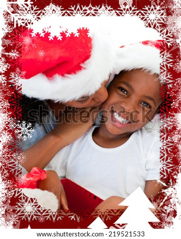 Mother kissing her daughter at Christmas against christmas themed frame - stock photo