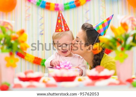 Mother kissing her happy while baby checking present - stock photo