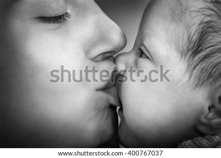 Mother kissing her newborn baby. Close-up portrait, black and white - stock photo