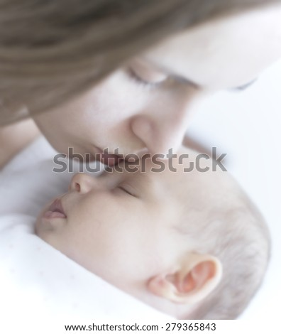mother kissing her newborn 8-week, gentleness and tenderness - stock photo