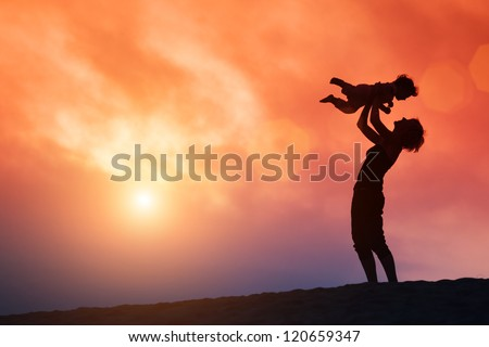 Mother lifting toddler child in air over scenic sunset sky - stock photo