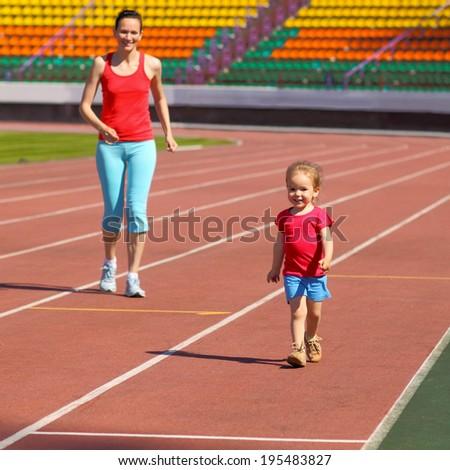 Mother & little daughter running around the stadium. Child runs away from mom at the stadium. - stock photo