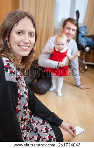 Mother looking at camera while father playing with baby girl in domestic room - stock photo