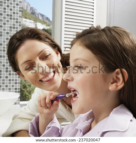 Mother Looking at Daughter Brushing Her Teeth - stock photo