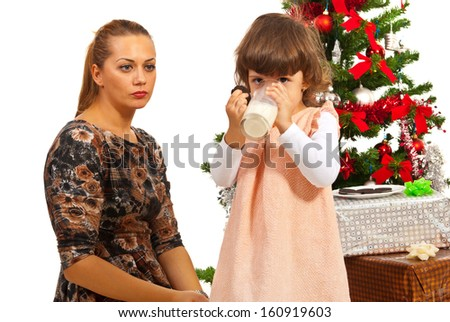 Mother looking at her daughter who drinking milk in front of Christmas tree - stock photo