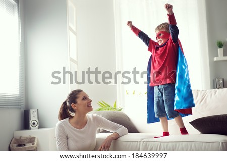 Mother looking at little superhero with fists raised standing on sofa. - stock photo