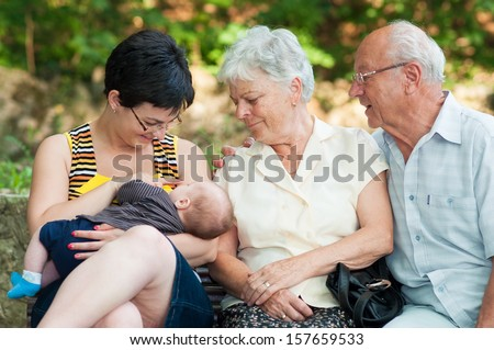 Mother looks at the kid sucking a breast - outdoor - stock photo