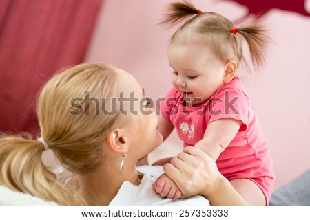 Mother looks playing with baby. Maternity happiness. - stock photo