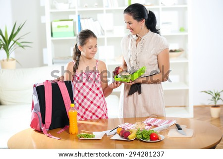 Mother making breakfast for her children in the morning and a snack for school - stock photo