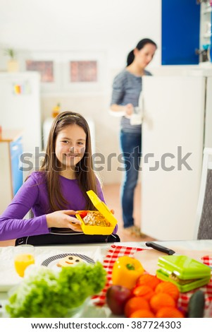 Mother making breakfast for her children in the morning and a snack for school at home - stock photo