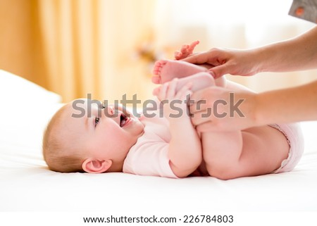 mother massaging or doing gymnastics to baby girl - stock photo