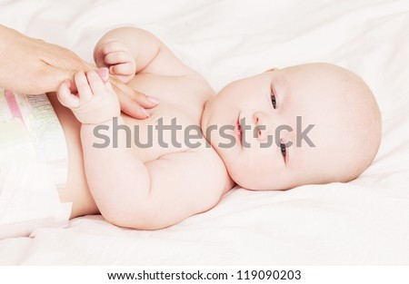 Mother massaging the belly of her four month old baby in bed at home - stock photo