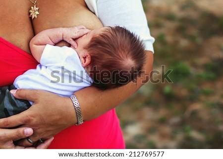 Mother nursing her 3 week old daughter -- image taken at Davis Creek Regional Park in Reno, Nevada, USA - stock photo