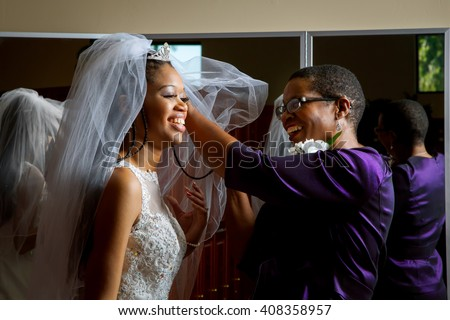 Mother of the bride adjusts her daughter's veil on her wedding day.  Beautiful, African American women, smiling while getting the daughter ready for her wedding.  - stock photo