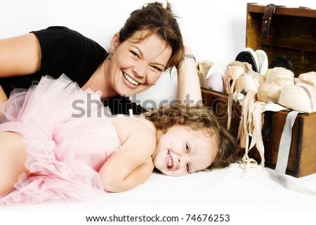 Mother of toddler ballet girl lying on the floor - stock photo