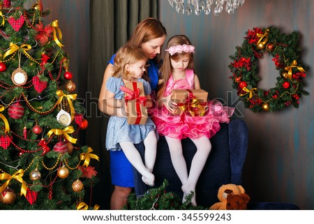 Mother of two daughters gave gifts near a Christmas tree. New Year. Holiday and fun. Merry Christmas. Holiday at home. 2017 - stock photo