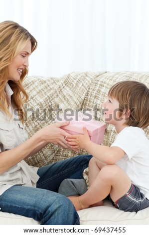 Mother offering present to her son on the sofa - stock photo