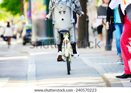 Mother on bike with child chair - stock photo