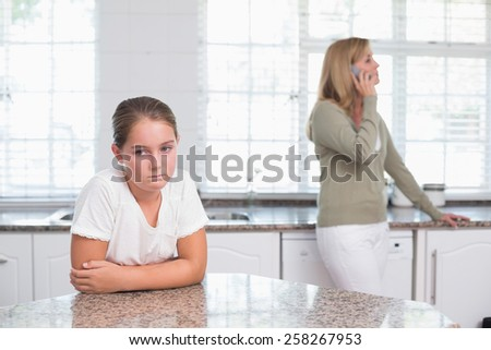 Mother on the phone while daughter sulking at home in the kitchen - stock photo