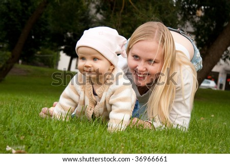 Mother outdoor playing with her daughter - stock photo