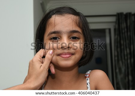 Mother pampering child. Little / small Indian girl / child / kid, smiling chubby cheeky, North India. Asian girl, 4 year cute look, black hair, long black hair, passport photo, hand on cheeks - stock photo