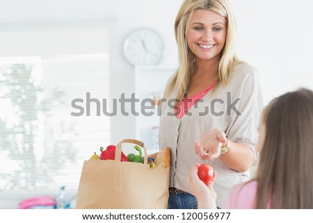 Mother passing tomato to child from paper grocery bag in ktichen - stock photo