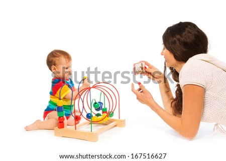 Mother photograph her little toddler boy playing with puzzle developing toy with camera on cell phone - stock photo