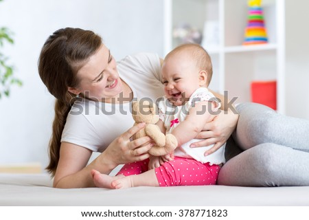 Mother plaing with her daughter baby - stock photo