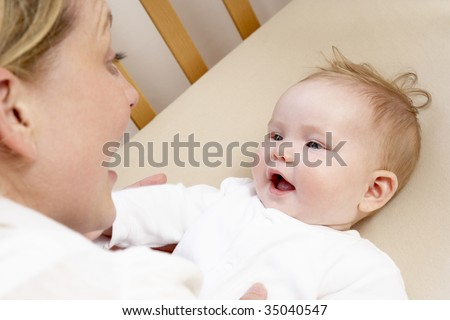 Mother Playing With Baby In Cot - stock photo