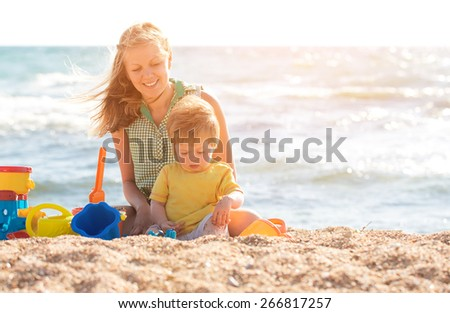 Mother playing with child on the beach - stock photo
