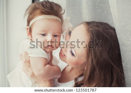 Mother playing with cute baby girl indoor - stock photo