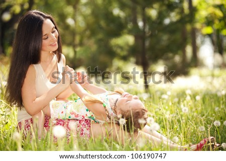 Mother playing with daughter in the park - stock photo