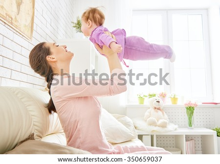 mother playing with her baby in the living room - stock photo
