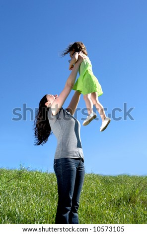Mother playing with her daughter in a meadow - stock photo