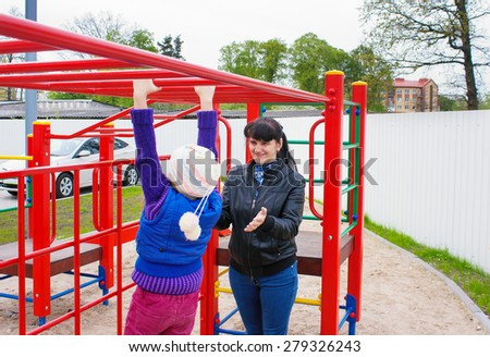 mother playing with her daughter on the playground - stock photo