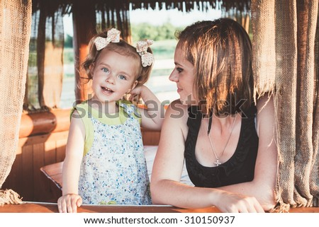 mother playing with her daughter sitting on the bench, childhood, fun, motherhood - stock photo