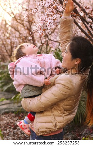 Mother Playing with her Infant Daughter amongst the Flowers - stock photo