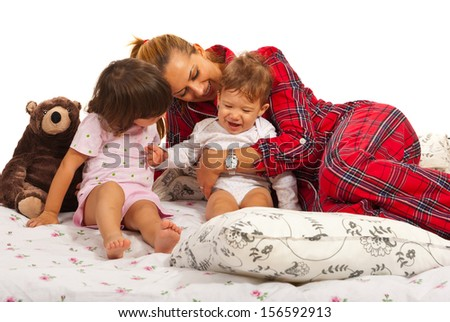 Mother playing with her kids in the bed and having fun together - stock photo