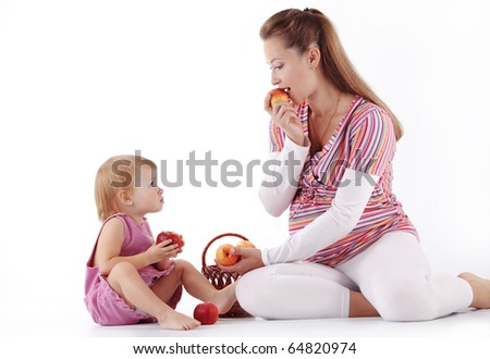 Mother playing with her little daughter studio shot - stock photo