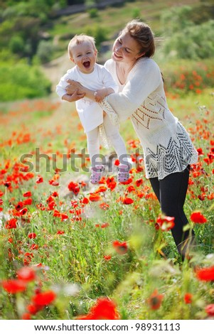 Mother playing with her toddler child in poppy field - stock photo