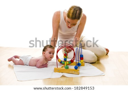 Mother playing with newborn baby an the floor, isolated against white background. - stock photo