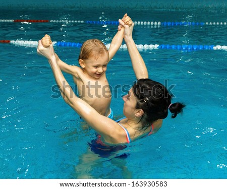 Mother plays with little son in the pool - stock photo
